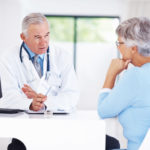 Male doctor talking to older woman