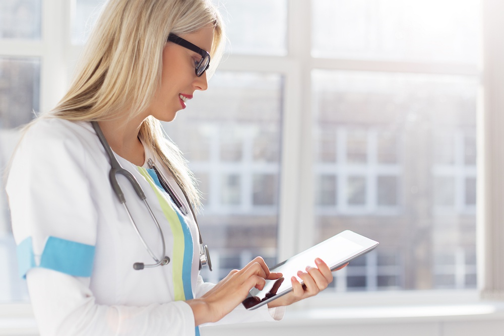 doctor looking at patient's medical records on tablet