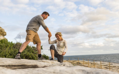 Active and fit mature couple helping each other while hiking in Sydney, Australia