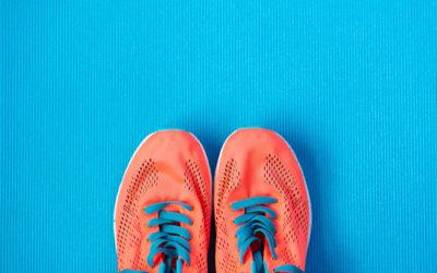 Orange tennis shoes standing on blue floor